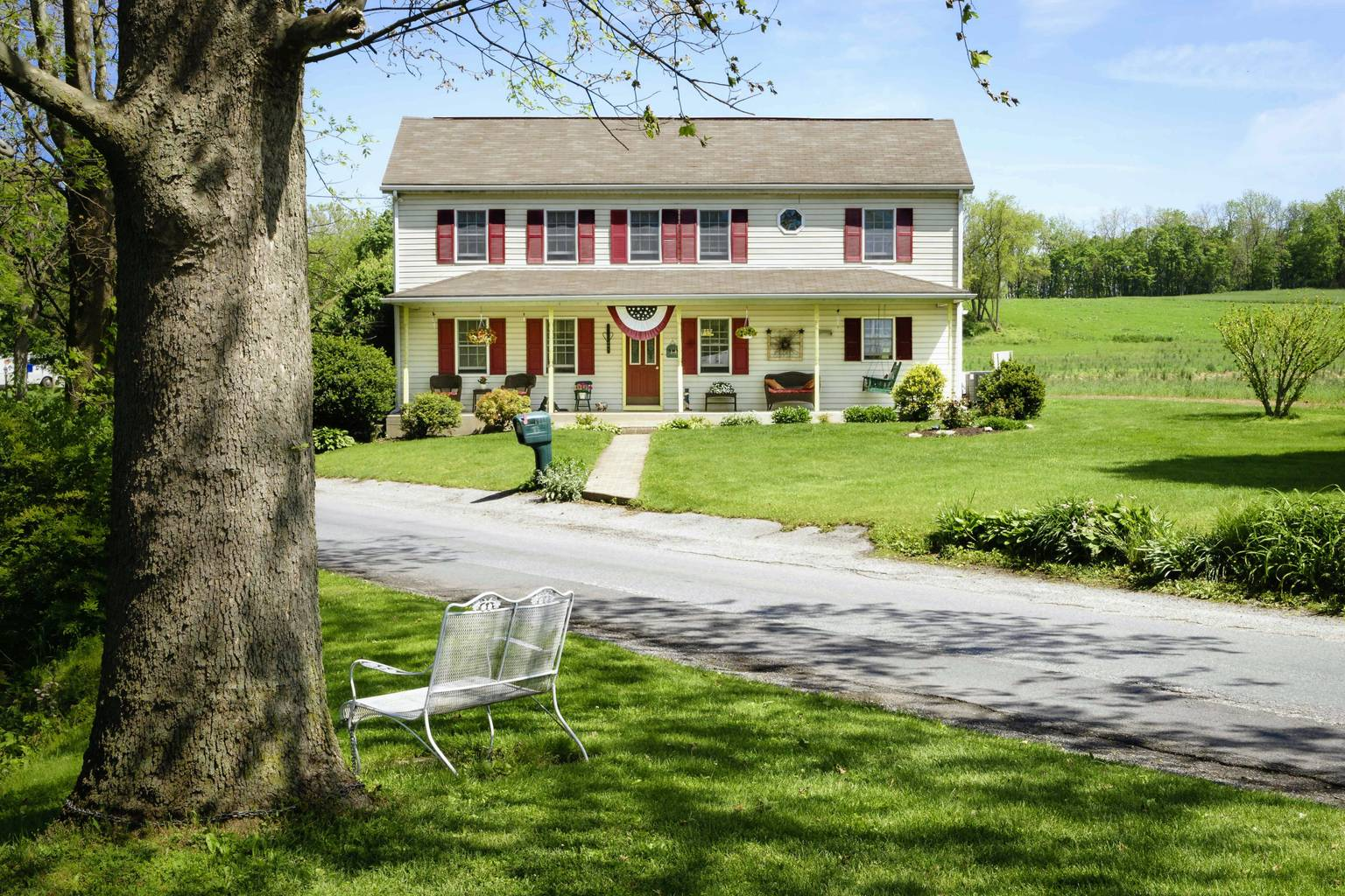 A large lawn in front of a house at Red Cardinal Bed & Breakfast.