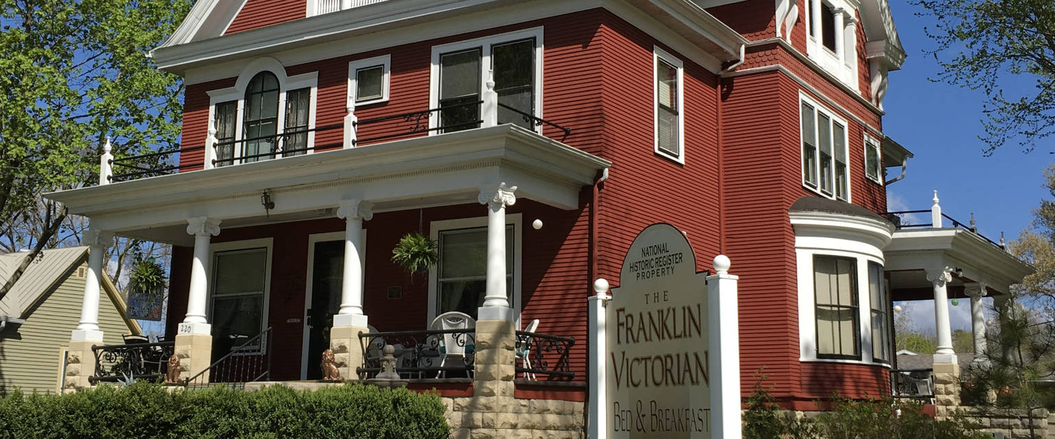 A house that has a sign on the side of a building at Franklin Victorian Bed and Breakfast.