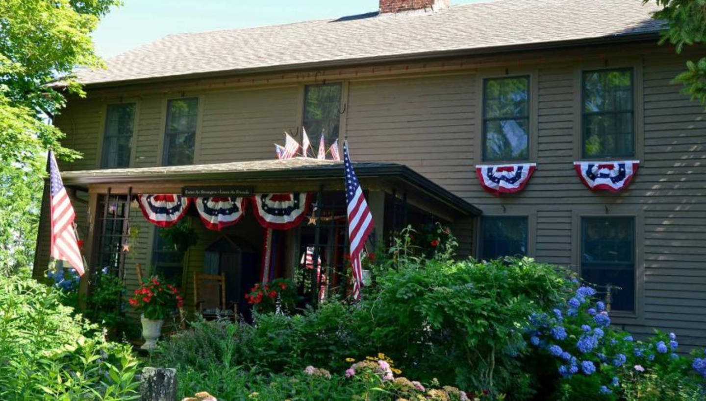 A house with bushes in front of a brick building at Roseledge Country Inn and Farm Shop LLC.