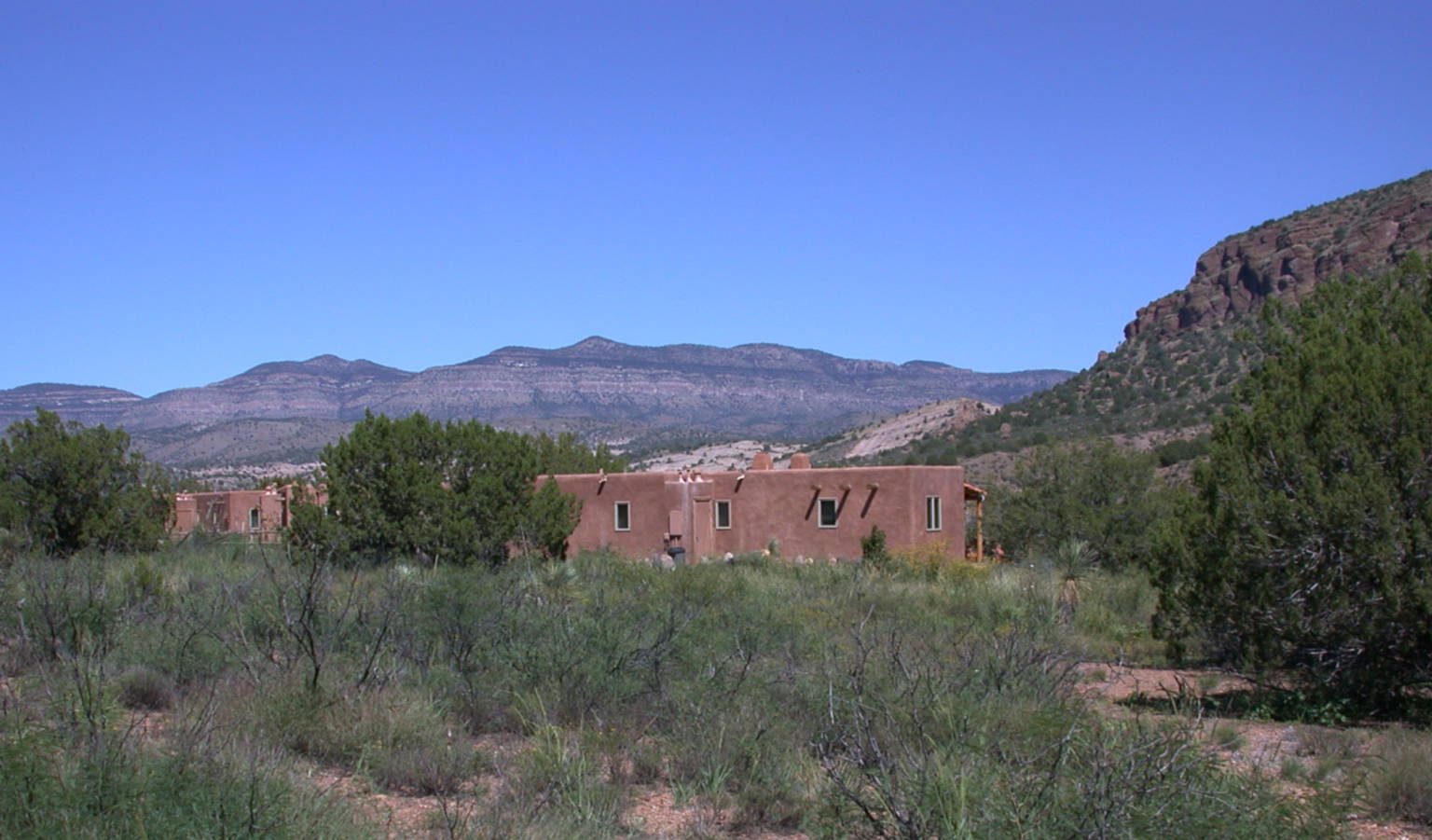A house with a mountain in the background at Casitas de Gila Guesthouses.
