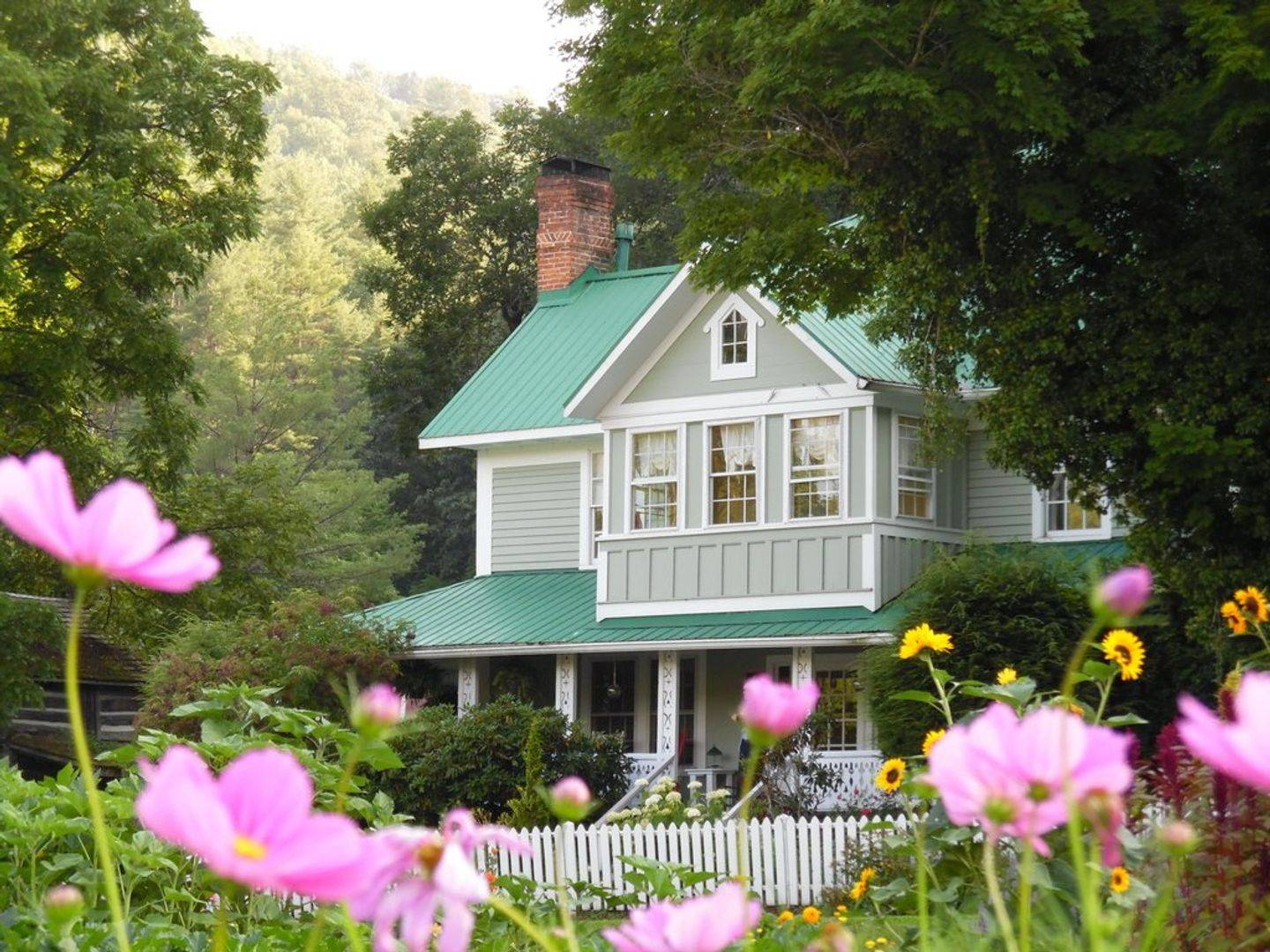A close up of a flower garden in front of a house at The Mast Farm Inn.
