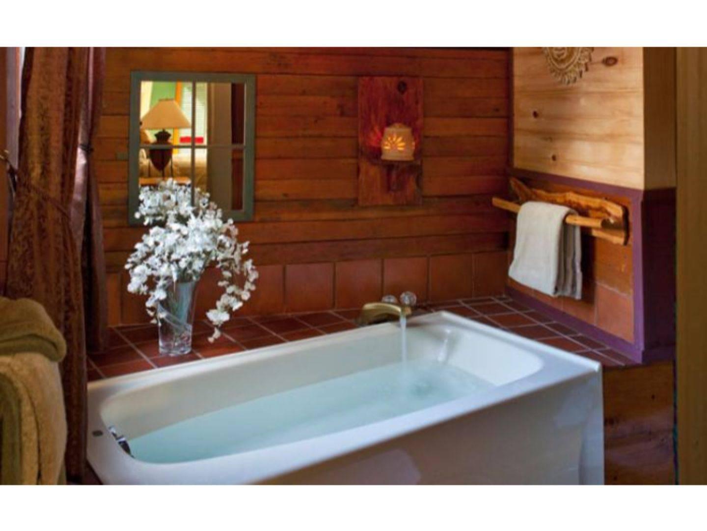 A large white tub sitting next to a sink at Abbey's Lantern Hill Inn.