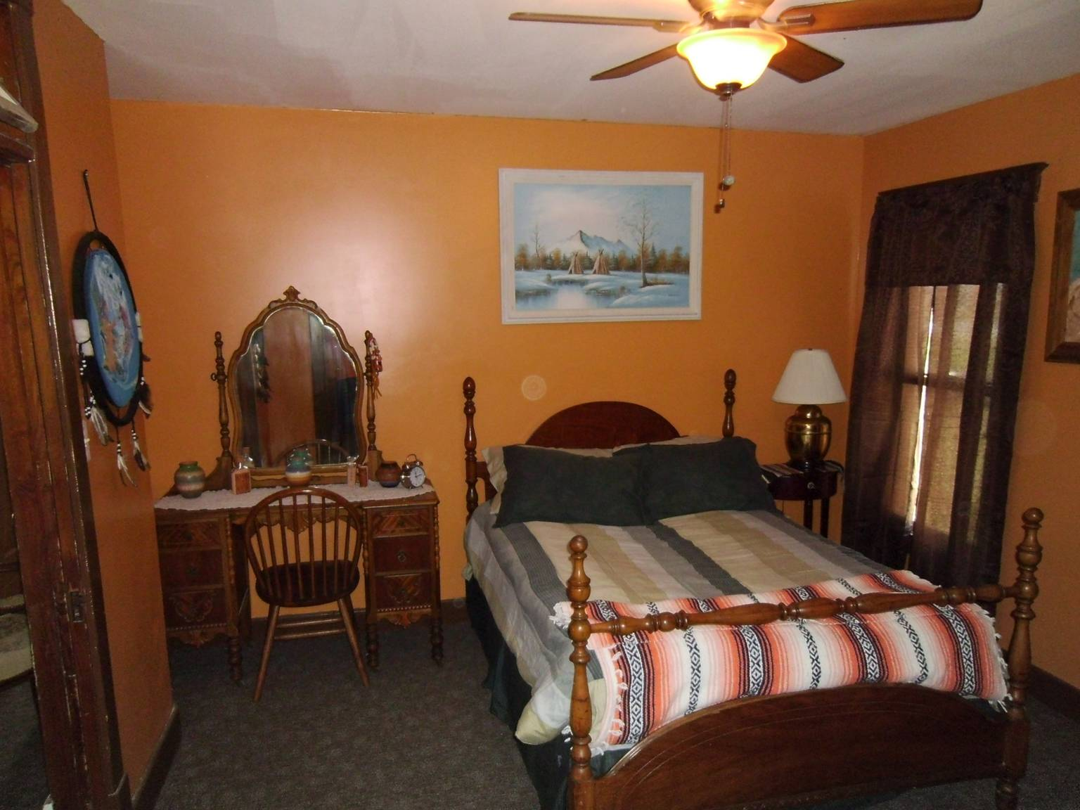 A bedroom with a bed and a chair in a room at Loess Hills Bed and Breakfast.