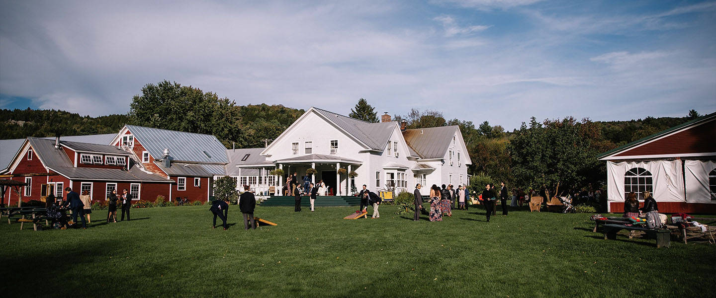 A group of people in a field in front of a house at Lareau Farm B&B.