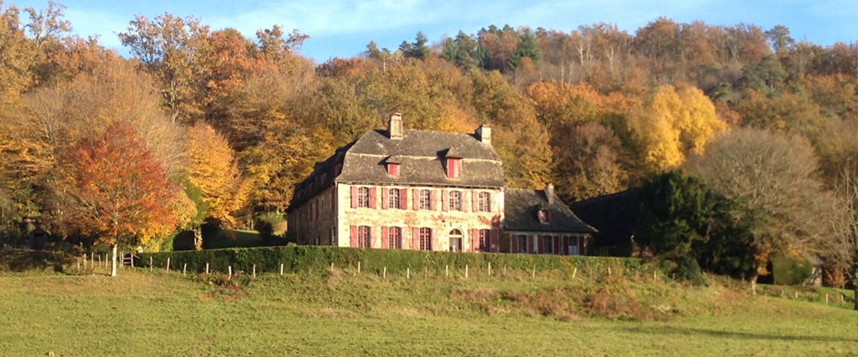 A castle on top of a lush green field at Chambre d'hôtes de charme Le Pradel.