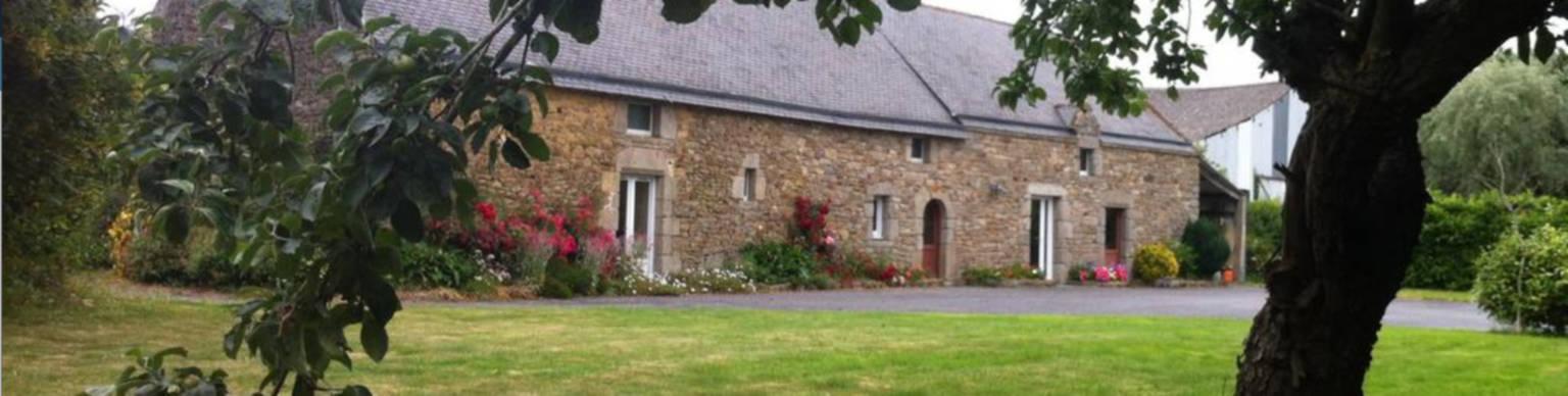 A large brick building with grass in front of a house at La Longère d'Hélène.