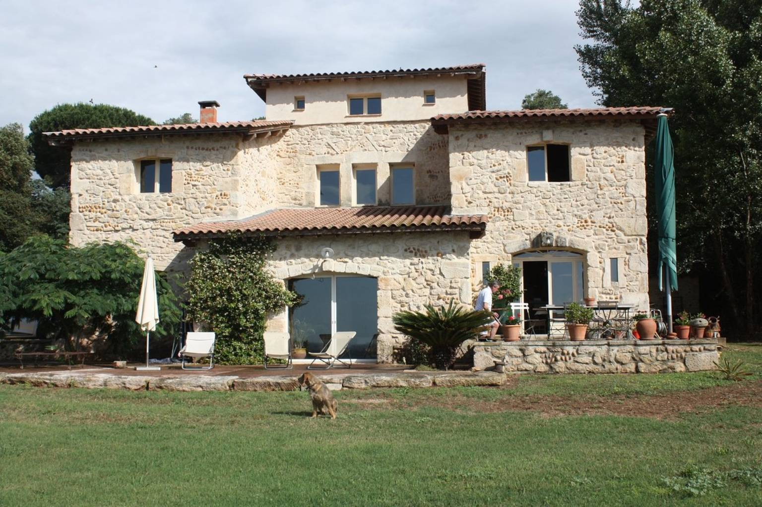 A large brick building with grass in front of a house at Chambres Anne et Oliver Ross.