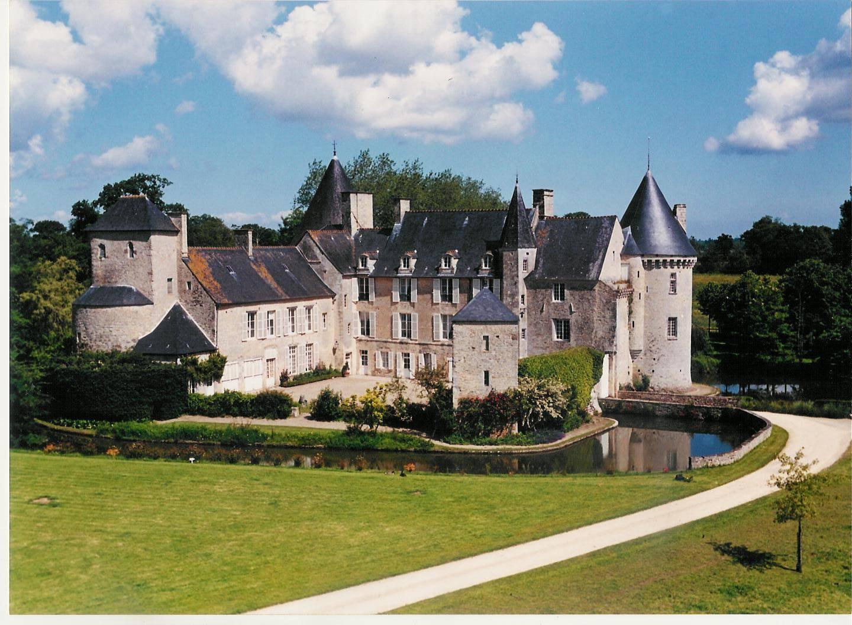 A castle on top of a lush green field at Château de Colombières.