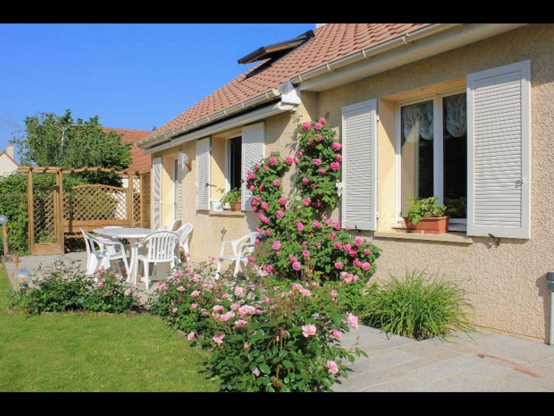A close up of a flower garden in front of a house at La maison du Parc.