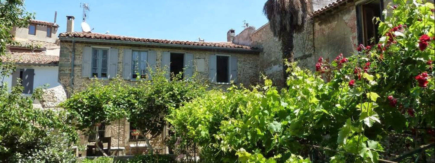 A house with bushes in front of a building at Maison Trivalle.
