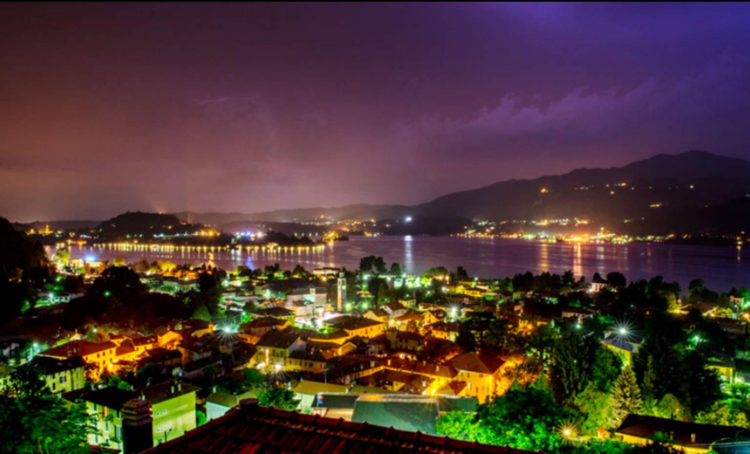 A view of a city at night at B&B Il Barsot.