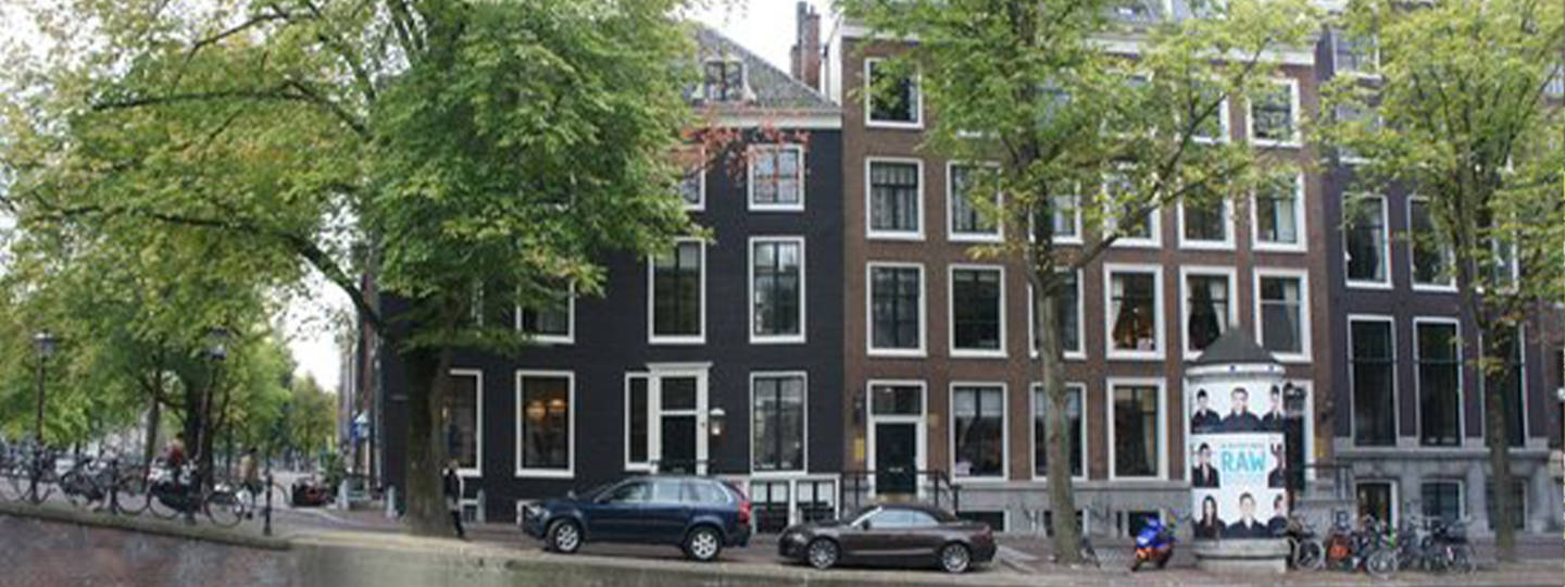 A street with cars parked on the side of anne frank house at Mokum Suites.