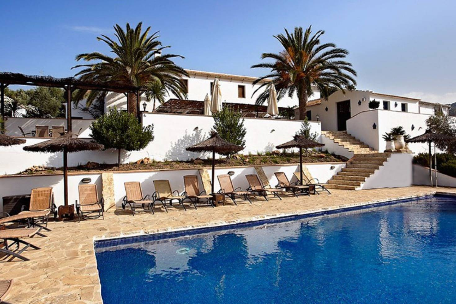 A pool next to a palm tree in front of a building at Casa Rural El Olivar.