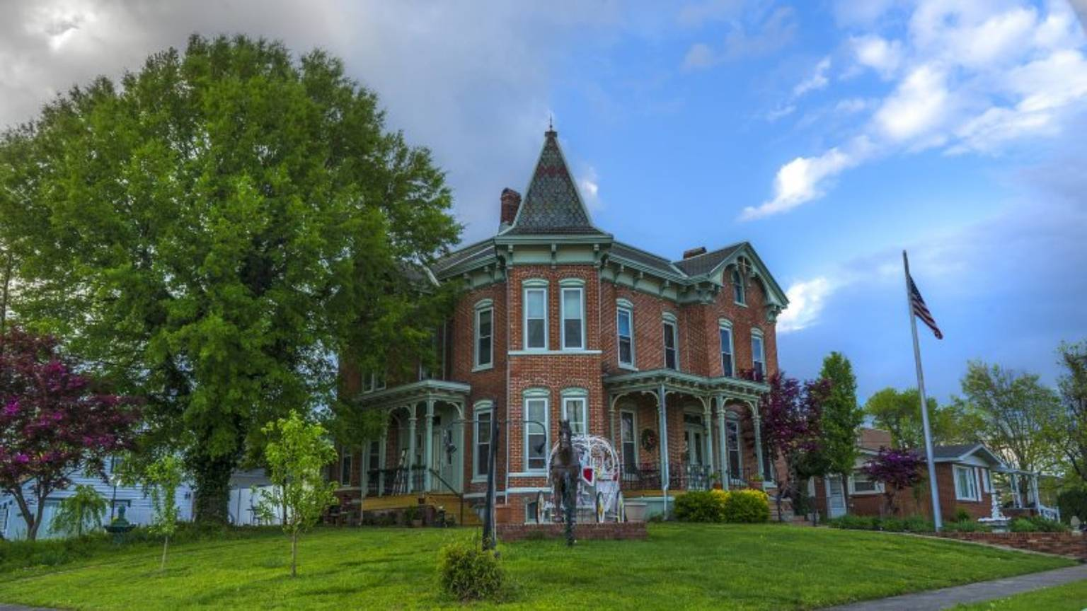 A large brick building with grass in front of a house at Summers Riverview Mansion Bed And Breakfast.