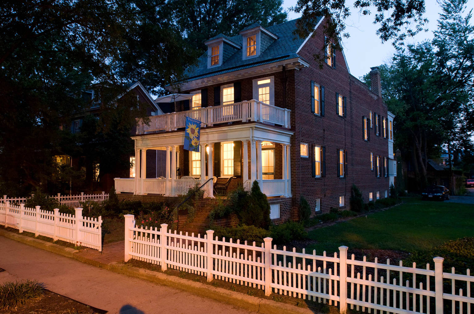 A house with a fence in front of a building at Museum District Bed & Breakfast.