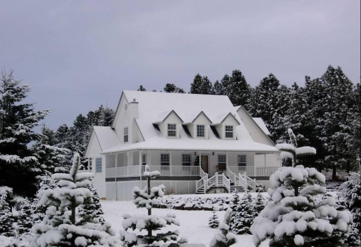 A house covered in snow at BlueBird Hill Farm B&B.