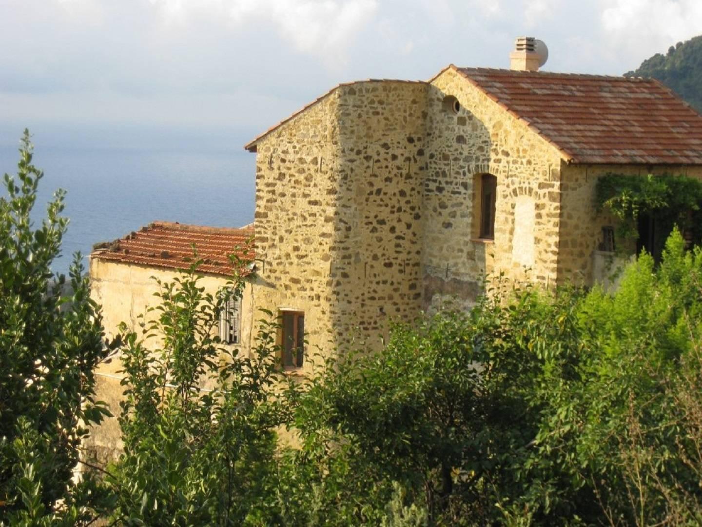 A house with bushes in front of a brick building at LA TERRAZZA DI CASE BASTEI .
