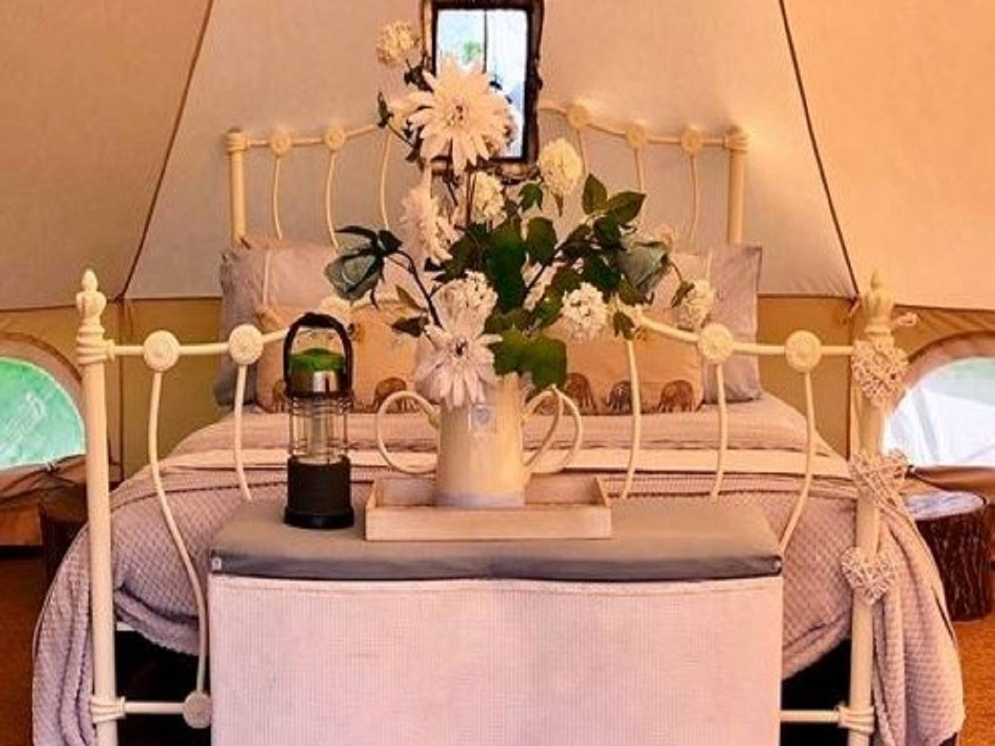 A room filled with furniture and vase of flowers on a table at Lane House B&B.