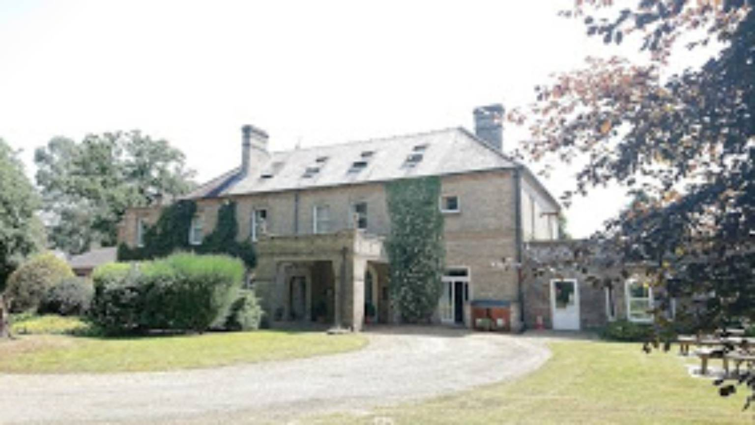 A large brick building with grass in front of a house at Broom Hall Country Hotel.