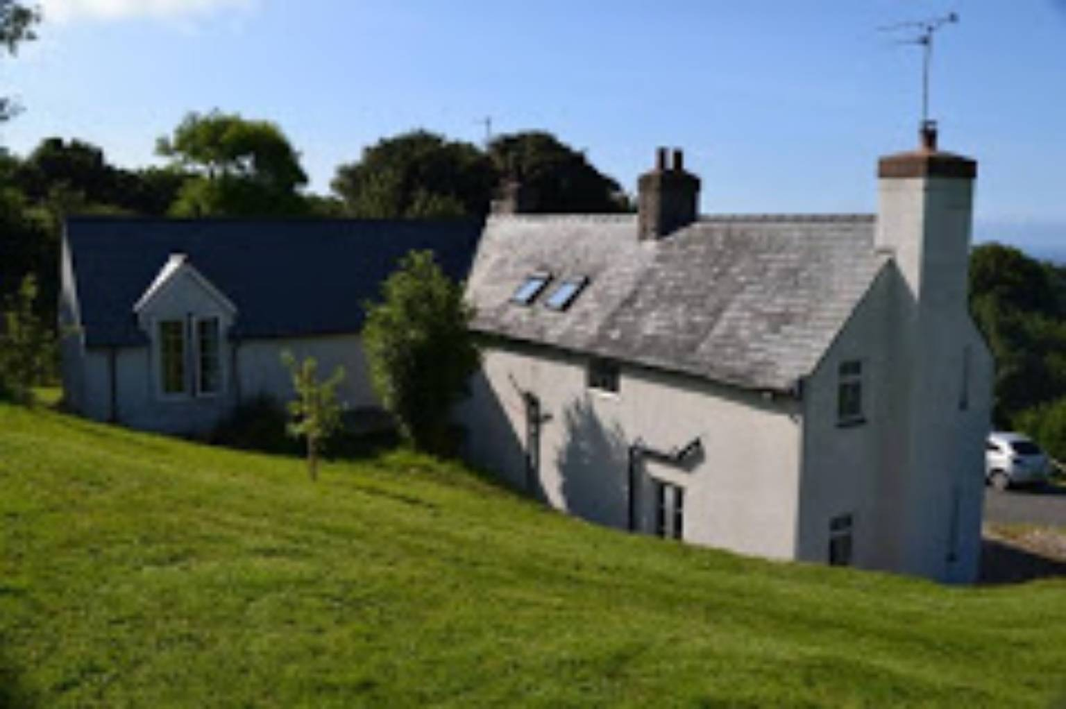 A castle on top of a lush green field at Bryn Goleu Bed and Breakfast.