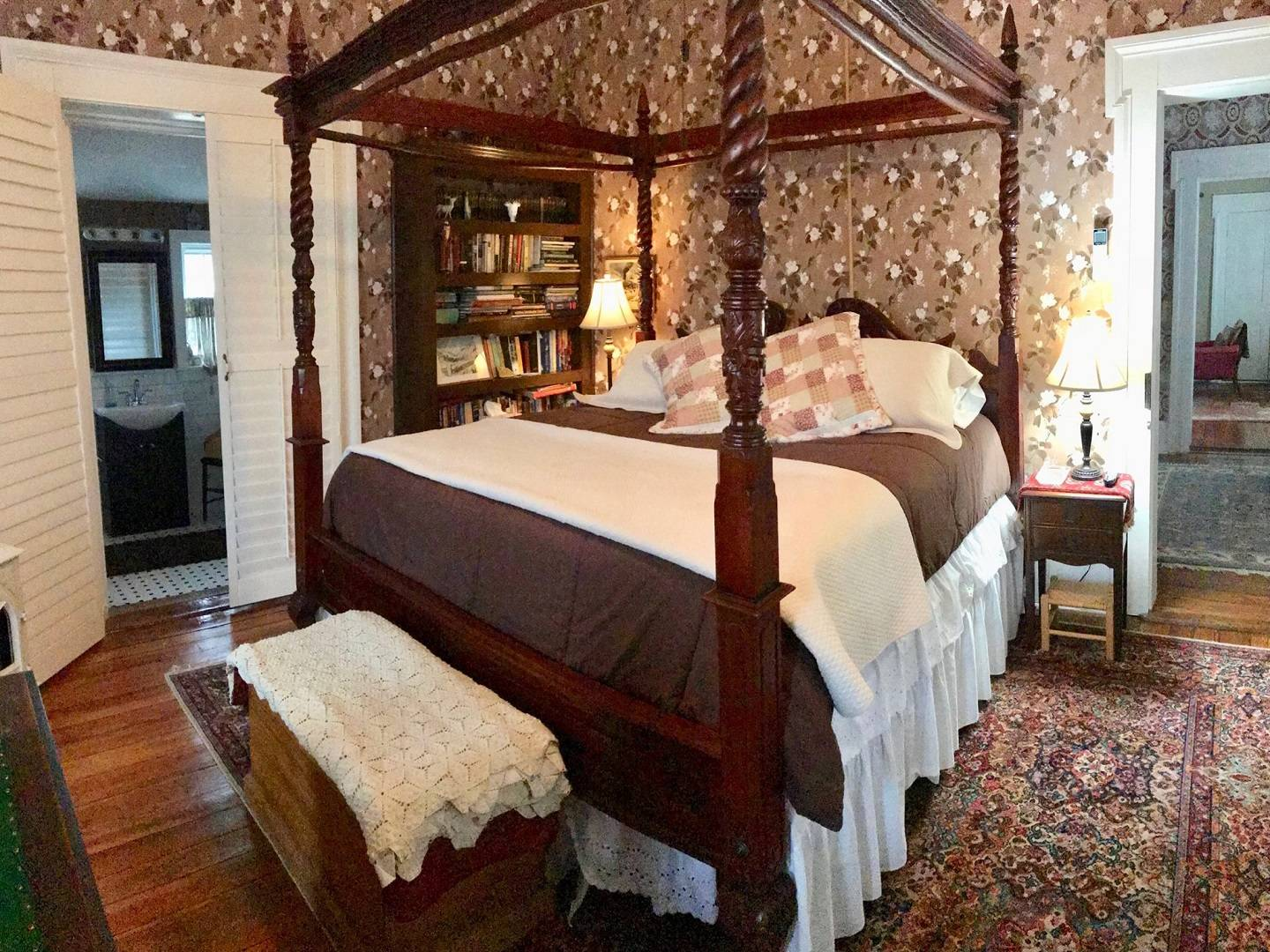 A bedroom with a bed and a chair in a room at  25 East Main B & B.