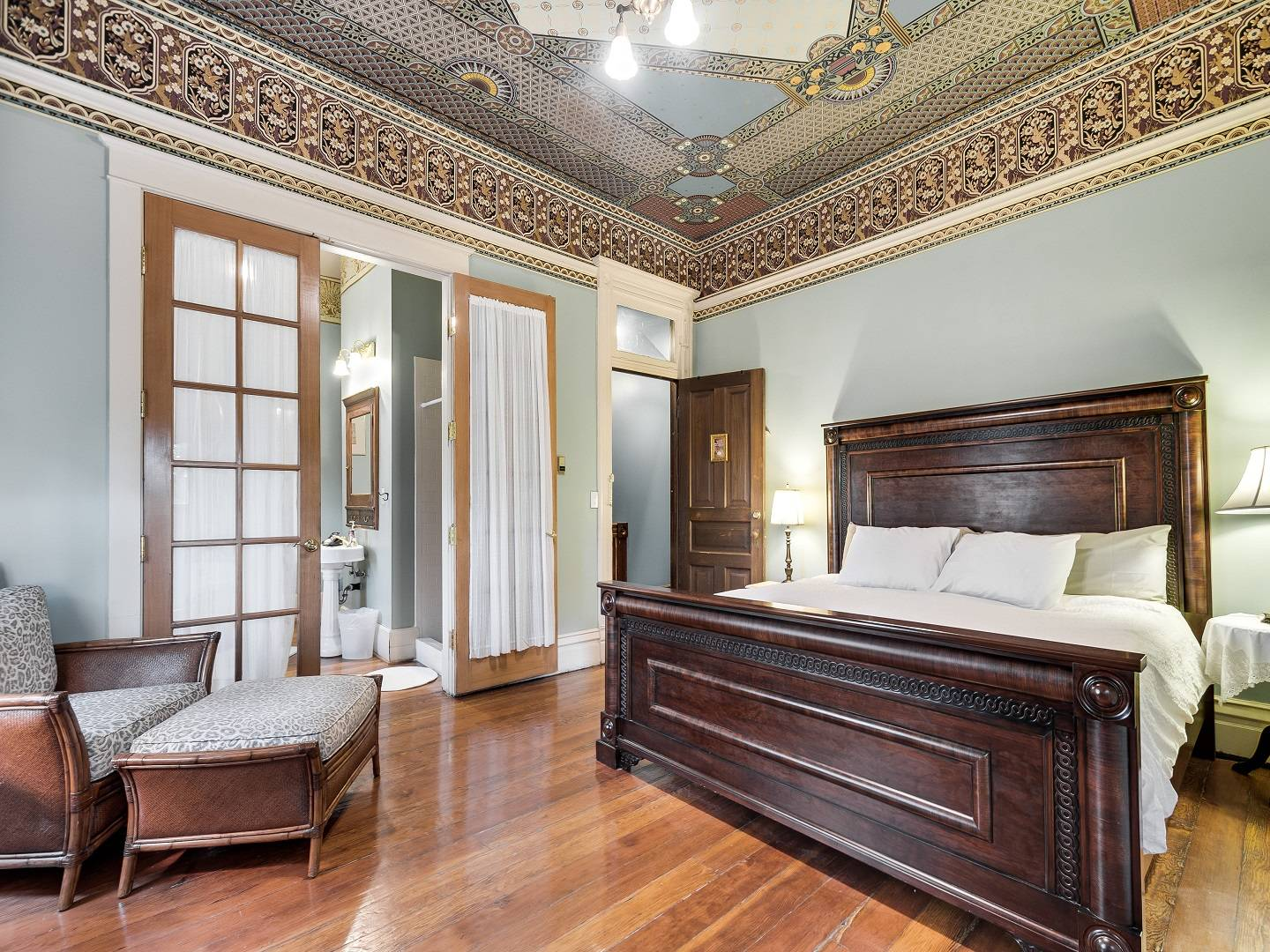 A bedroom with a bed and a chair in a room at Lumber Baron Inn.