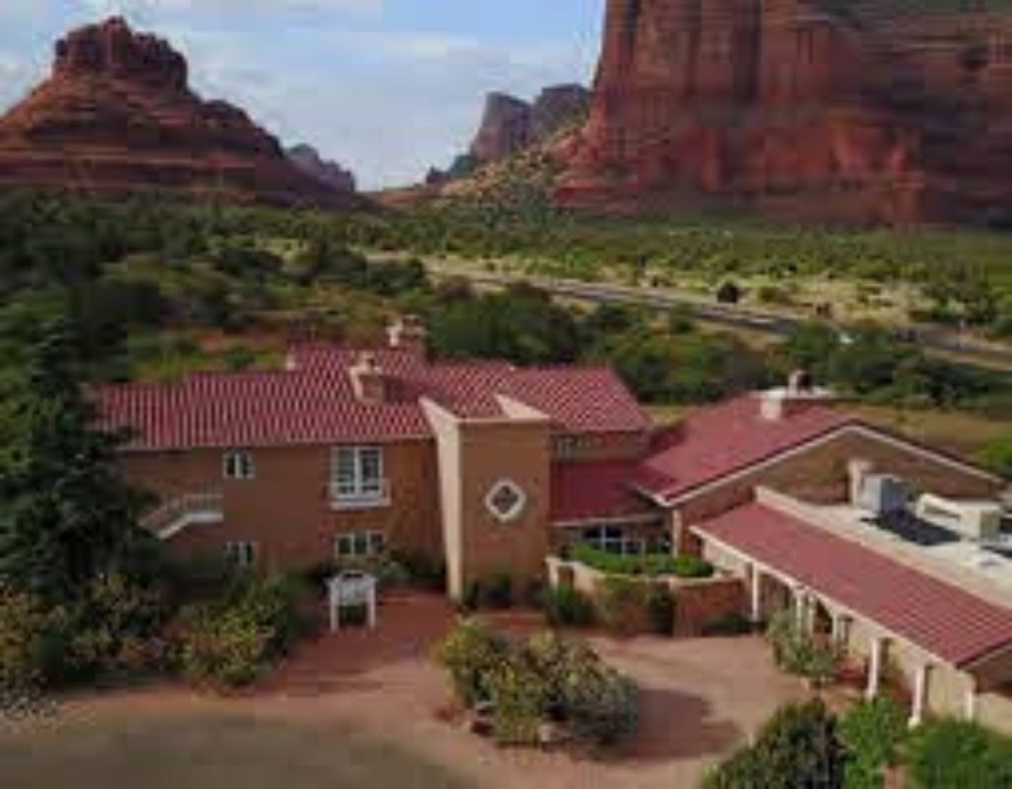 A large brick building with grass and trees at Canyon Villa Bed & Breakfast Inn of Sedona.