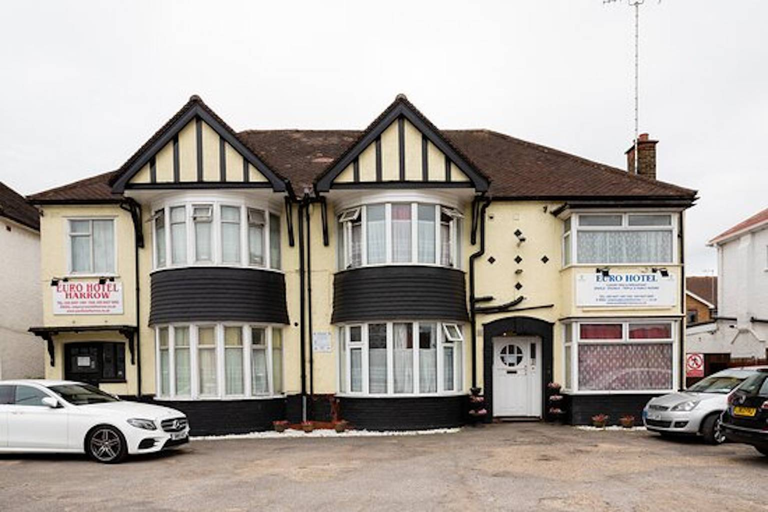A car parked in front of a house at EURO HOTEL HARROW.
