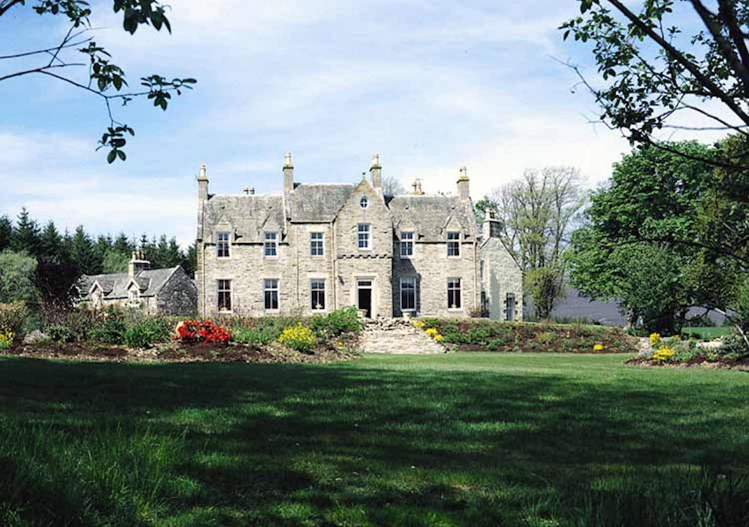 A castle on top of a lush green field at Glenlivet House .
