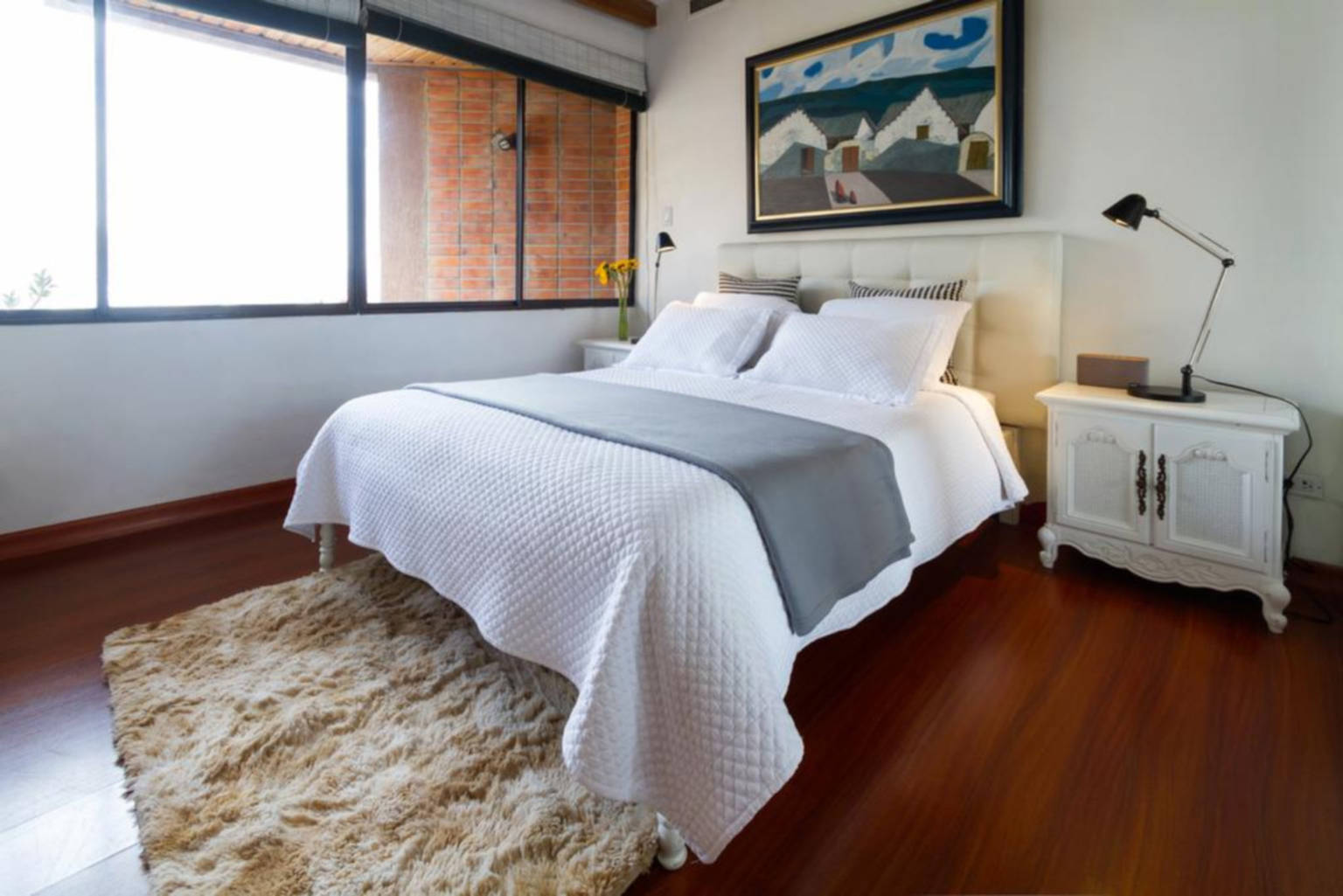 A bedroom with a bed and desk in a room at The Penthouse Lodge.